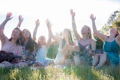 Девушки сидя совместно в травянистом поле поя и играя музыку Стоковые Изображения