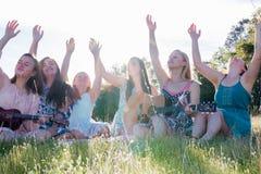 Девушки сидя совместно в травянистом поле поя и играя музыку Стоковое фото RF