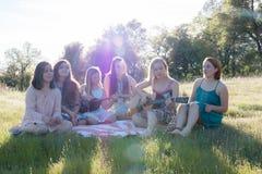 Девушки сидя совместно в травянистом поле поя и играя музыку Стоковое Изображение RF