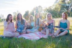 Девушки сидя совместно в травянистом поле поя и играя музыку Стоковая Фотография RF