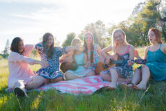 Девушки сидя совместно в травянистом поле поя и играя музыку Стоковое Изображение