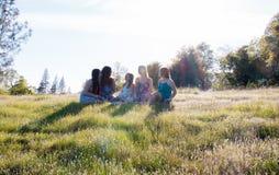 Девушки сидя совместно в травянистом поле с солнечным светом наверху Стоковая Фотография