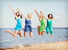 Девушки скача на пляж Стоковое Фото