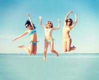 Девушки скача на пляж Стоковая Фотография