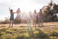 Девушки скача совместно смотрящ на яркий заход солнца Стоковое Фото