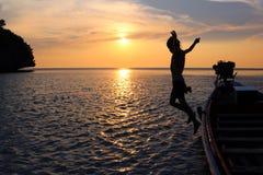 Девушки скачут от шлюпки длинного хвоста с заходом солнца Стоковая Фотография