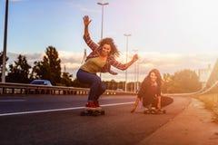 Девушки скейтборда ехать longboards опускают дорогу стоковая фотография rf