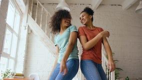 Девушки смешанной гонки молодые красивые танцуя на кровати совместно имея отдых потехи в спальне дома стоковая фотография