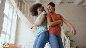 Девушки смешанной гонки молодые красивые танцуя на кровати совместно имея отдых потехи в спальне дома Стоковые Изображения RF