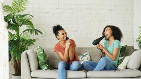 Девушки смешанной гонки молодые смешные танцуют петь при фен для волос и гребень сидя на софе Сестры имея отдых потехи в жить Стоковые Изображения