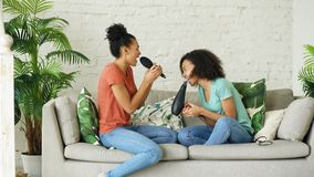 Девушки смешанной гонки молодые смешные танцуют петь при фен для волос и гребень сидя на софе Сестры имея отдых потехи в жить Стоковые Изображения RF