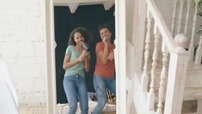 Девушки смешанной гонки молодые смешные танцуют петь с феном для волос и гребнем перед зеркалом Сестры имея отдых потехи внутри видеоматериал