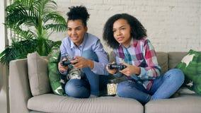 2 девушки смешанных гонки курчавых сидя на игре кресла утешают компютерные игры с gamepad и имеют потеху дома Стоковое фото RF