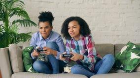 2 девушки смешанных гонки курчавых сидя на игре кресла утешают компютерные игры с gamepad и имеют потеху дома Стоковые Фотографии RF