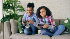 2 девушки смешанных гонки курчавых сидя на игре кресла утешают компютерные игры с gamepad и имеют потеху дома Стоковое Изображение RF