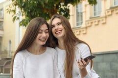 2 девушки смеются над потехой пока говорить, развевая smartphone Стоковые Изображения RF