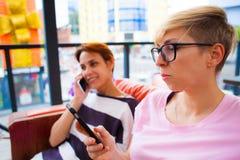 Девушки смотрят в их телефоны Стоковое фото RF