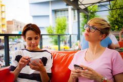 Девушки смотрят в их телефоны Стоковое Изображение
