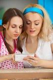 девушки смотря изображения мобильного телефона Стоковые Изображения RF