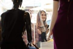 Девушки смотря дисплей магазина одежды Стоковая Фотография