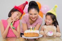 Девушки смотря мать с тортом на вечеринке по случаю дня рождения Стоковая Фотография RF