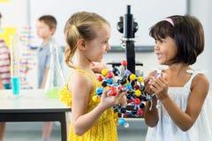 Девушки смотря один другого пока держащ модель дна Стоковое фото RF
