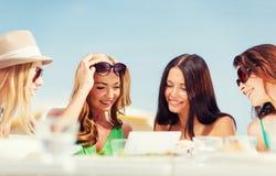 Девушки смотря ПК таблетки в кафе Стоковое Изображение RF