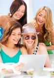 Девушки смотря ПК таблетки в кафе Стоковая Фотография
