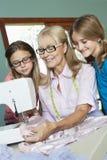 Девушки смотря ткань бабушки шить Стоковые Фото