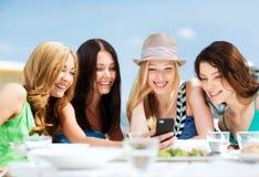 Девушки смотря smartphone в кафе на пляже Стоковые Изображения RF