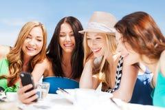 Девушки смотря smartphone в кафе на пляже Стоковая Фотография