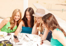 Девушки смотря smartphone в кафе на пляже Стоковые Фотографии RF