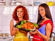 Девушки совместно держат поднос жареной курицы на кухне Стоковые Изображения RF