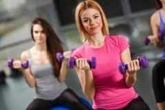 Девушки спорта в спортзале работая с гантелями Стоковая Фотография
