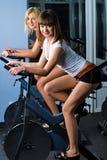 Девушки спорта pedaling на имитаторе Стоковые Фото