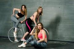 3 девушки спорт в зале фитнеса на велосипеде стоковая фотография rf