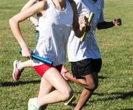 Девушки средней школы участвуя в гонке реле на поле травы Стоковая Фотография