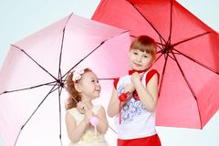 2 девушки стоят под зонтиками Стоковая Фотография