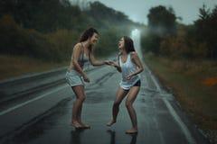 Девушки стоя в дожде на проезжей части Стоковые Изображения RF