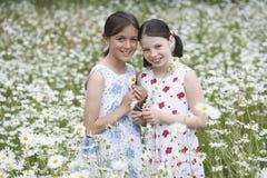 Девушки стоя в луге цветка Стоковые Изображения RF