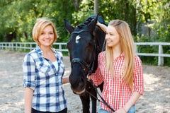 Девушки стоя наряду с лошадью Стоковая Фотография