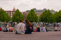 Девушки студента сидя на стенде, отдыхая в парке, весна в Москве стоковое изображение