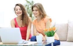 2 девушки студента смотря компьтер-книжку экранируют пока сидящ на кресле Стоковое Изображение RF