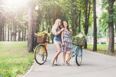 Девушки счастливого boho шикарные едут совместно на велосипедах в парке Стоковые Изображения RF
