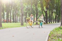 Девушки счастливого boho шикарные едут совместно на велосипедах в парке Стоковое Изображение RF