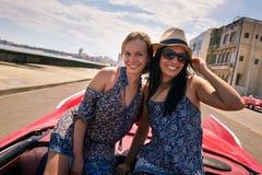 Девушки счастливых пар туристские на винтажном автомобиле Гаване Кубе Стоковая Фотография