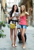 Девушки с багажом и картой Стоковая Фотография