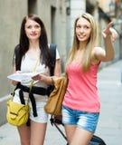 Девушки с багажом и картой Стоковые Фотографии RF