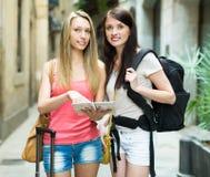 Девушки с багажом и картой Стоковое Изображение