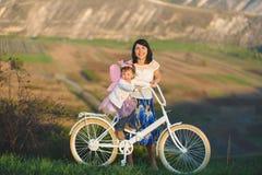 Девушки с велосипедом на заходе солнца Стоковые Изображения RF